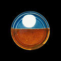 A round plate, the lower half orange, and the upper half blue with a large white circle in the centre