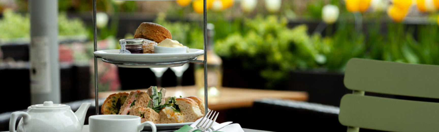 A tower of cakes, sandwiches and scones alongside teacup and teapot
