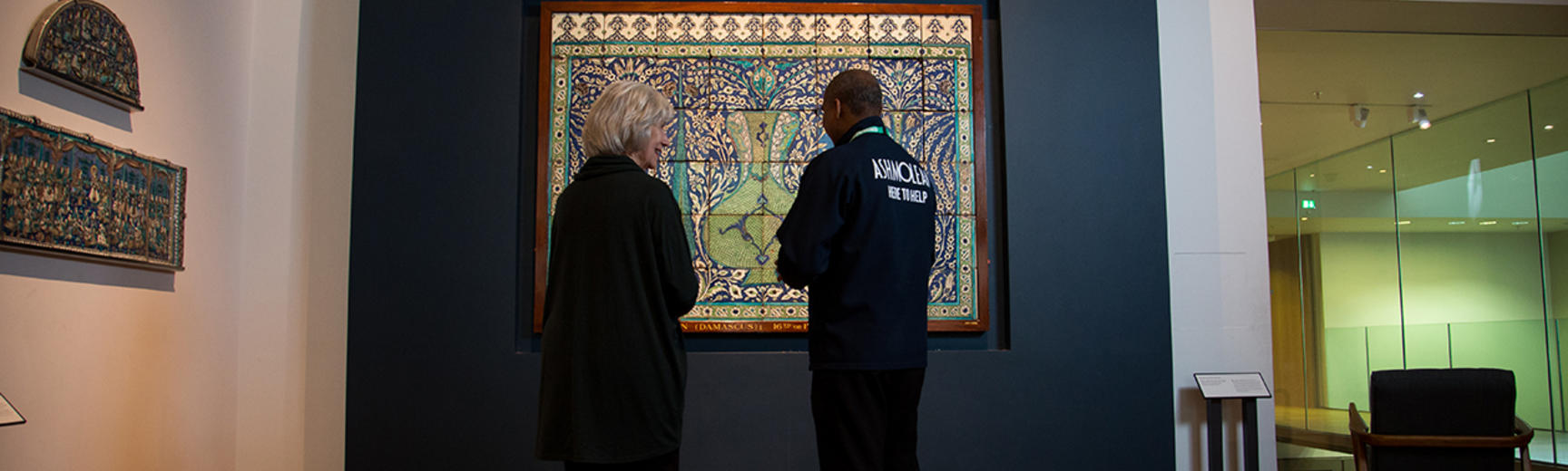 A visitor engagement assistant is telling a visitor some information about the Islamic Tiles in front of them