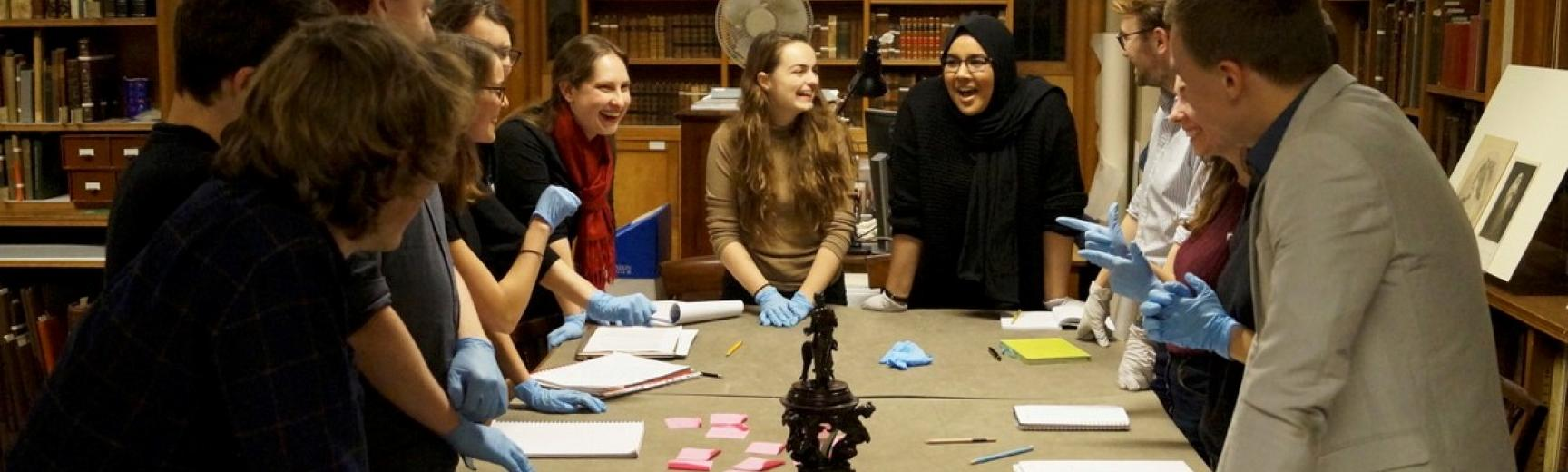 A group of students around a table of objects in a museum study room