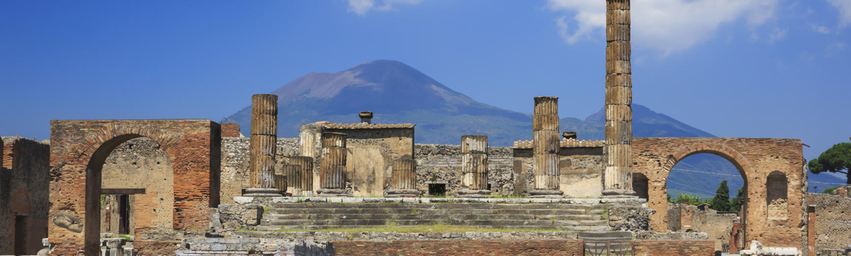 Ruins at the historical site of Pompeii, with Mount Vesuvius in the distance