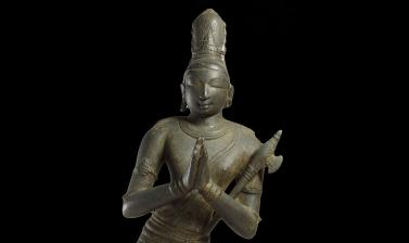 Close-up on figure of Hindu Saint Chandikeshvara, holding an axe, showing head and torso.