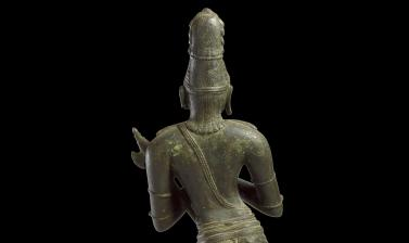 Close-up on figure of Hindu Saint Chandikeshvara, showing head and torso from behind.