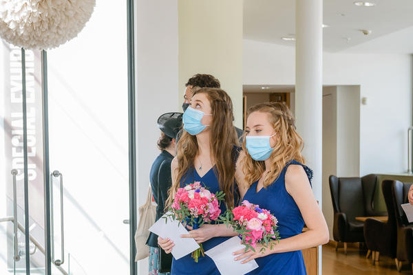 Portrait photo of two bridesmaids dressed in blue wearing face masks