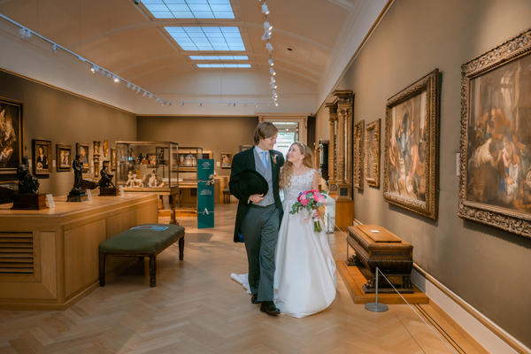 Portrait photo of bride and groom in european art gallery