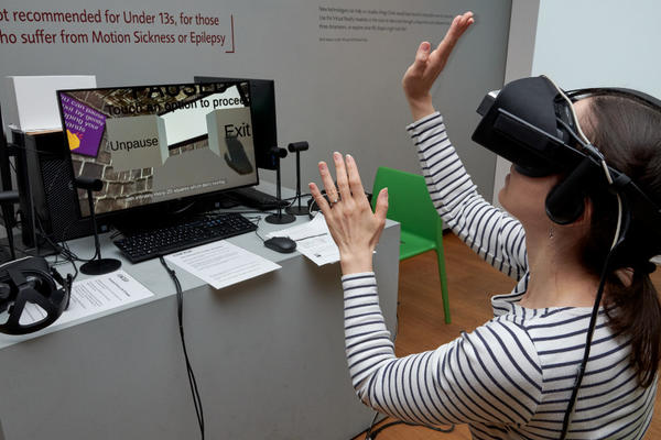 A photo from the Dimensions Exhibition of a girl in an interactive VR headset.