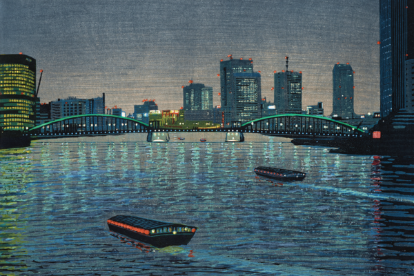 A view of a city by the water at night, with boats passing in the foreground