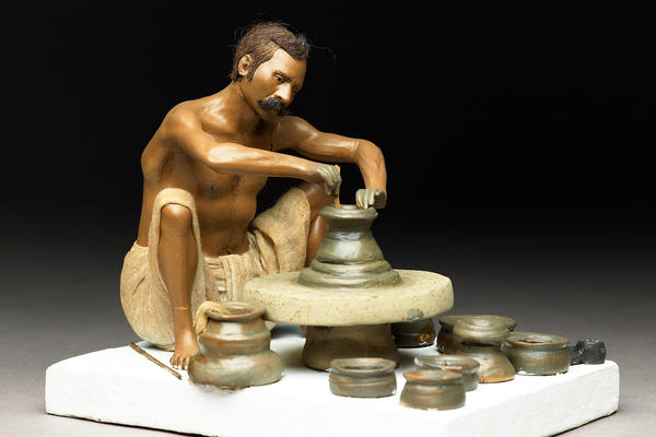 Model depicting a potter turning a pot on a wheel