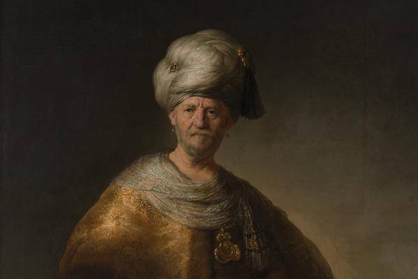 A painting of a white man in oriental dress consisting of a yellow cape and white turban, the background is plain, by Rembrandt.