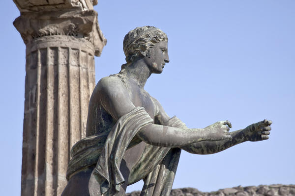 A grey statue of apollo stands with arms outstretched, with blue sky and Roman columns behind it