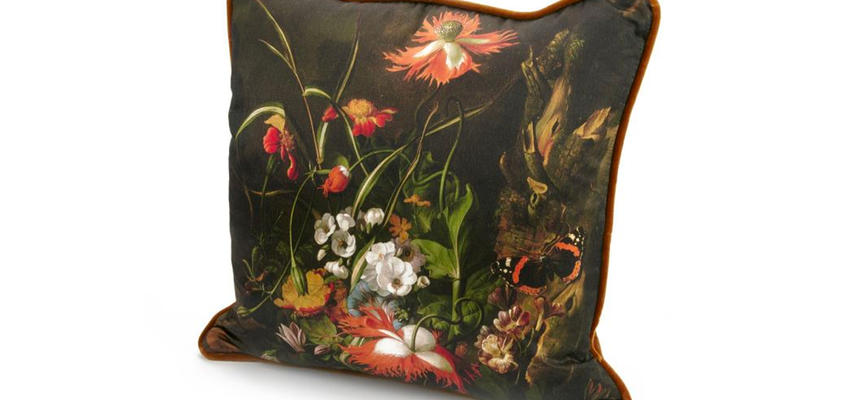 A photograph of a cushion decorated with a still life by Rachel Ruysch.