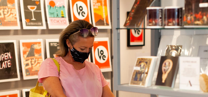 A visitor browses prints in a rack in the Museum's gift shop
