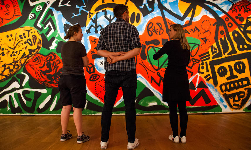 Dr Lena Fritsch with installation team in front of A. R. Penck painting